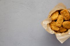 Chicken nuggets in a paper box on a gray background. Overhead, from above, flat lay. Space for text.  stock photography
