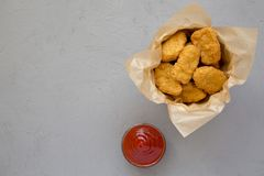 Chicken nuggets in a paper box, ketchup on a concrete background. Overhead, from above, flat lay. Space for text.  stock photos