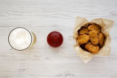Chicken nuggets in a paper box, ketchup and glass of cold beer on a white wooden background. Overhead, from above, flat lay.  stock photos