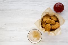 Chicken nuggets in a paper box, ketchup and glass of cold beer on a white wooden background, overhead view. Top view, from above,. Flat lay. Copy space royalty free stock image