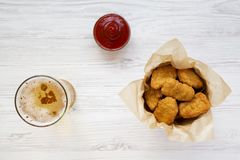 Chicken nuggets in a paper box, ketchup and glass of cold beer on a white wooden background, top view. Overhead, from above, flat. Lay. Close-up royalty free stock photo