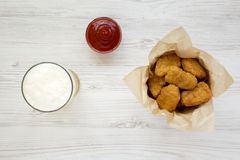 Chicken nuggets in a paper box, ketchup and glass of cold beer on a white wooden surface. Overhead, from above, flat lay.  stock photos