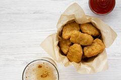 Chicken nuggets in a paper box, ketchup and glass of cold beer on a white wooden surface, top view. Overhead, from above, flat lay. Copy space stock images