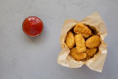 Chicken nuggets in a paper box, ketchup on a gray background. Overhead, from above, flat lay.  stock photo