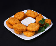 Chicken nuggets on plate with mayo over black Royalty Free Stock Photos