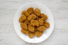 Chicken nuggets on a plate on a white wooden background, top view. Overhead, from above, flat lay. Close-up.  stock image