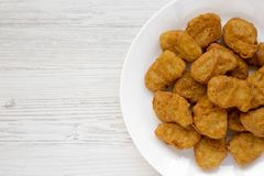 Chicken nuggets on a plate on a white wooden surface, top view. Overhead, from above, flat lay. Copy space.  royalty free stock photos