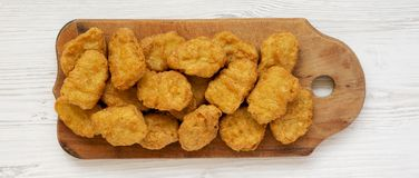 Chicken nuggets on a rustic wooden board on a white wooden surface, top view. Flat lay, from above, overhead.  royalty free stock photography