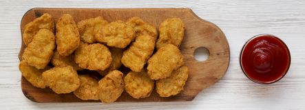Chicken nuggets on a rustic wooden board on a white wooden surface, top view. Flat lay, from above, overhead.  stock image