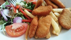 Chicken nuggets with salad and chips Royalty Free Stock Photography