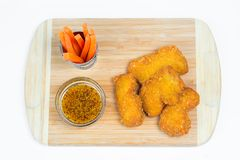Chicken nuggets with sauces on wooden board stock images