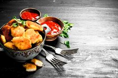 Chicken nuggets with tomato sauce and greens. On the black chalkboard Royalty Free Stock Image