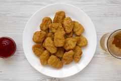 Chicken nuggets on a white plate, ketchup and glass of cold beer on a white wooden background. Overhead, from above, flat lay.  royalty free stock images