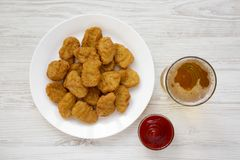 Chicken nuggets on a white plate, ketchup and glass of cold beer on a white wooden background. Overhead, from above, flat lay.  royalty free stock photos