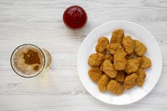 Chicken nuggets on a white plate, ketchup and glass of cold beer on a white wooden surface. Overhead, from above, flat lay.  stock photos