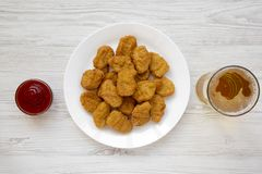 Chicken nuggets on a white plate, ketchup and glass of cold beer on a white wooden surface. Overhead, from above, flat lay.  royalty free stock images