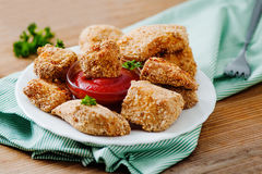 Chicken nuggets on the white plate with tomato sauce Stock Image