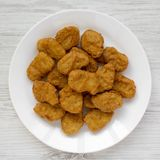 Chicken nuggets on a white plate on a white wooden background, top view. Overhead, from above, flat lay. Closeup.  stock images
