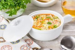 Chicken orzo soup in a white crock on wooden background. Italian soup with orzo pasta.  Royalty Free Stock Photos