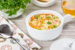 Chicken orzo soup in a white crock on wooden background. Italian soup with orzo pasta. Glass of white wine Stock Images
