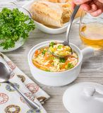 Chicken orzo soup in a white crock on wooden background. Italian soup with orzo pasta. Chef`s hand holding a ladle. Bread. Glass of wine Royalty Free Stock Photo