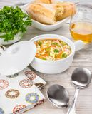 Chicken orzo soup in a white crock on wooden background. Italian soup with orzo pasta. Bread. Glass of wine Stock Photo