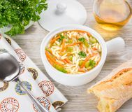 Chicken orzo soup in a white crock on wooden background. Italian soup with orzo pasta. Bread, parsley, wine Royalty Free Stock Image