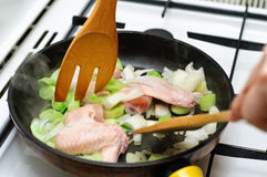 Chicken on a pan. Chicken wings and leek on a pan with utensils Stock Photo