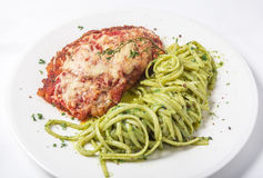 Chicken with parmesan cheese and linguine pasta in pesto sauce. On white background. Close-up Stock Photos