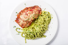 Chicken with parmesan cheese and linguine pasta in pesto sauce. On white background. Close-up top view Royalty Free Stock Image