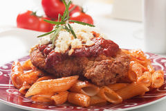 Chicken parmesan with macaroni pasta. Chicken parmesan, breaded chicken steak with tomato sauce and macaroni pasta Royalty Free Stock Images