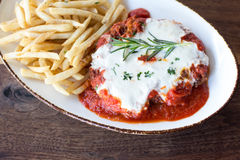 Chicken Parmesan. Chicken parmigiana topped with rosemary and french fries Royalty Free Stock Photos