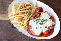 Chicken Parmesan. Chicken parmigiana topped with rosemary and french fries Stock Photo