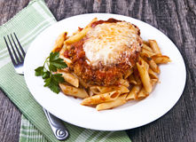 Chicken parmigiana. On a wood rustic table  served on top of pasta with marinara sauce Stock Images