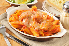 Chicken Parmigiana and Penne. A bowl of chicken parmigiana and penne with salad and dinner rolls Stock Images