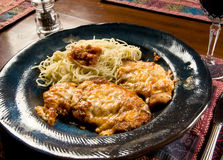 Chicken parmigiana. Serving of chicken parmigiana (chicken parmesan) with angle hair pasta Stock Images