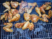 Chicken parts preparing on barbecue for dinner in the garden. Roasting for hungry people royalty free stock photo