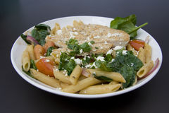 Chicken and pasta. Bowl of Penne pasta with grilled chicken, tomatoes, spinach and feta cheese Royalty Free Stock Image