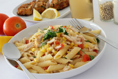 Chicken Pasta. A plate of chicken pasta sprinkled with Parmesan cheese with ingredients in the background Royalty Free Stock Image