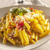 Chicken pasta. Yellow chicken pasta with parmesan cheese and chili pyree Stock Photo