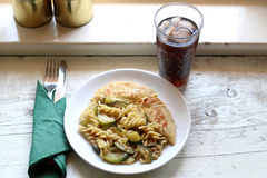 Chicken and Pasta. Chicken breasts, pasta and zucchini with melted cheese. Soda with ice in a tall glass. Selective focus Stock Photos