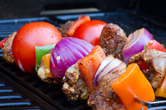 Chicken and pepper kebabs slowly cooking Royalty Free Stock Photo