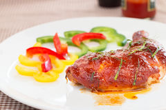 Chicken with pepper sauce. On white plate Royalty Free Stock Images