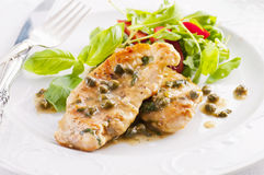 Chicken piccata. With capern and salad royalty free stock images
