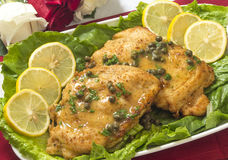 Chicken piccata for two. Romantic dinner for two of chicken piccata on a table with fresh roses stock photo
