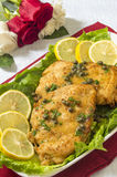 Chicken piccata for two. Romantic dinner for two of chicken piccata on a table with fresh roses royalty free stock photos