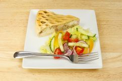 Chicken pie and salad on a tabletop. Chicken and ham pie with salad and a fork on a wooden tabletop Stock Photography