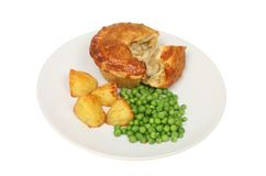 Chicken pie and veg. Chicken and mushroom pie with roast potatoes and peas on a plate isolated against white Royalty Free Stock Images