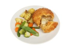 Chicken pie and veg. Chicken pie with roast potatoes and vegetables ona plate isolated against white royalty free stock images