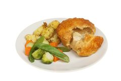 Chicken pie and vegetables. Chicken pie with roast potatoes, Brussel sprouts, carrots and mange tout on a plate isolated against white royalty free stock images